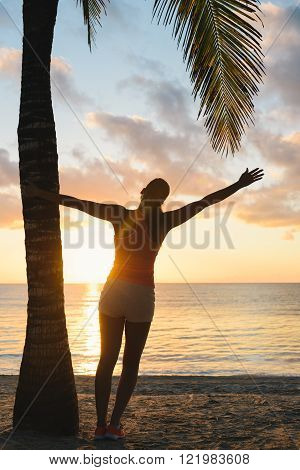 Blissful fitness woman enjoying outdoor summer sunrise or sunset workout at the beach. Happy female athlete exercising during vacation under tropical palms at Riviera Maya Mexico.