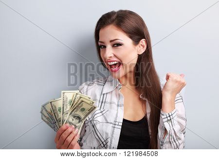 Happy young casual woman holding dollars and showing yes success sign with open mouth on blue background