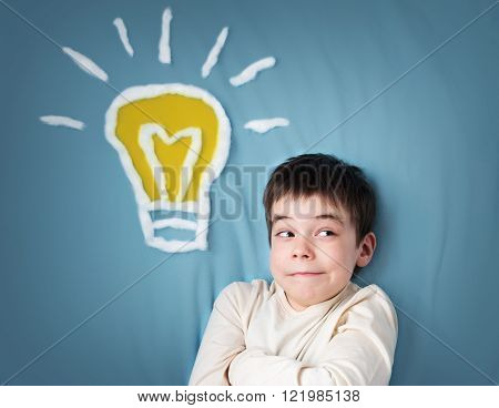 seven years old boy and a bulb near. Child with an idea
