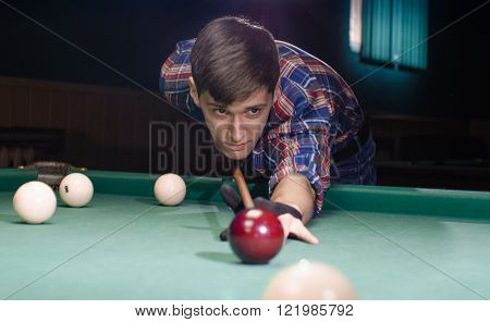 boy in focus aiming for shot of the billiard ball which isn't in focus
