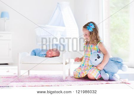 Cute little girl kissing newborn brother. Toddler kid meeting new born sibling. Infant sleeping in toy bed in white nursery. Kids playing. Siblings with small age difference. Children play and bond.