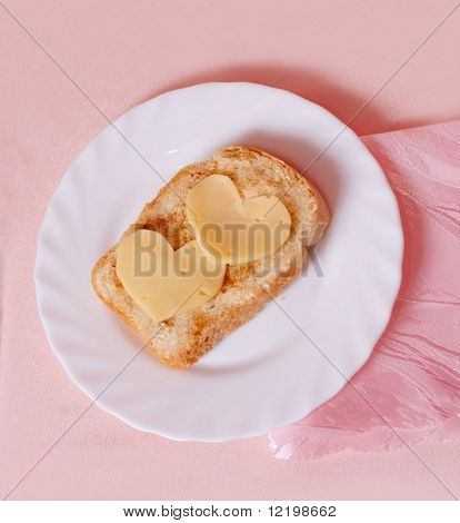 sandwich with cheese in the form of heart on pink background