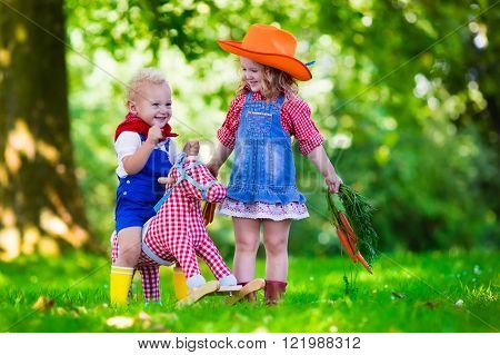Little boy and girl dressed up as cowboy and cowgirl playing with toy rocking horse in park. Kids play outdoors. Children in Halloween costumes at trick or treat. Toys for preschooler or toddler child