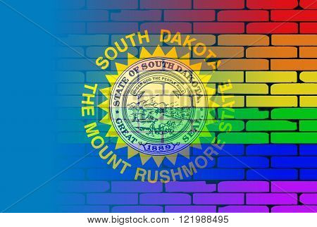 A well worn wall painted with a LGBT rainbow with the Iowa state flag