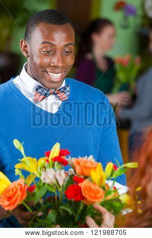 Handsome happy single African American male customer in a busy flower shop