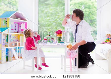 Happy family young father and his little daughter cute curly toddler girl wearing a dress playing together with doll house having toy tea party in a white sunny nursery