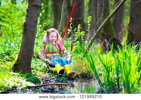 Child playing outdoors. Preschooler kid catching fish with red rod. 