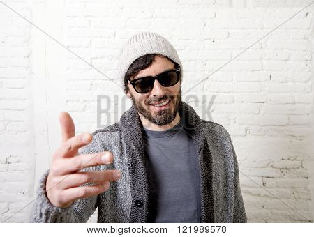 young attractive hipster and trendy style looking man smiling happy posing cool with attitude dressing informal wearing casual beanie beard and sunglasses in male fashion concept