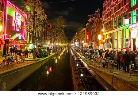 Amsterdam-May 1: Red light district (Wallen) at night with famous theatre Casa Rosso on the left hand side on May 12015 in Amsterdam the Netherlands.The Amsterdam Red Light District is one of the most iconic places in all of Europe famous for its liberal