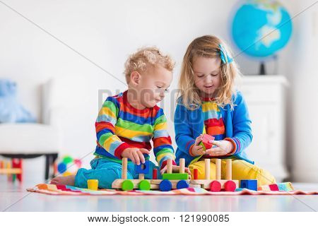 Children playing with wooden train. Toddler kid and baby play with blocks trains and cars. Educational toys for preschool and kindergarten child.