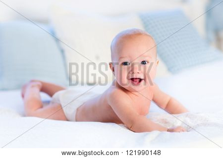 Baby boy wearing diaper in white sunny bedroom. Newborn child relaxing in bed.  ** Note: Shallow depth of field