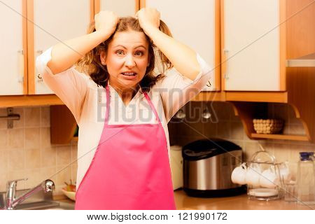 Frightened and worried woman wearing pink apron. Unhappy anxious and stressed housewife in kitchen. Negative facial emotion. Filtered
