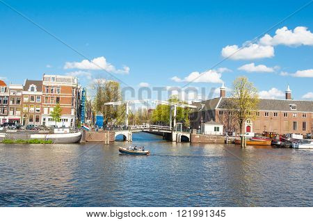 Amsterdam-April 30: Amsterdam cityscape Magere Brug also known as Skinny Bridge at the front and Hermitage Amsterdam on the left on April 30, 2015 the Netherlands.
