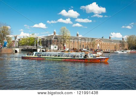 Amsterdam-April 30: Amsterdam cityscape tourists enjoy canal cruise Magere Brug also known as Skinny Bridge and Hermitage Amsterdam are visible on the background on April 30 2015 the Netherlands.