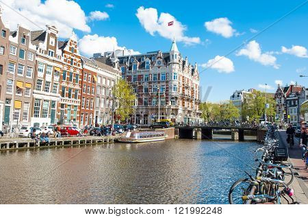 Amsterdam-April 30: Rokin canal with bikes parked along the bank Hotel de l'Europe is visible in the background tourists enjoy cityscape on the opposite side on April 30 2015 the Netherlands.