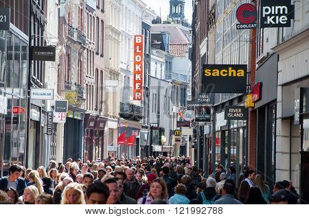 AMSTERDAM-APRIL 30: Kalverstraat shopping street in the midday people go shopping on April 30 2015. The Kalverstraat is a busy shopping street of Amsterdam the capital of the Netherlands.