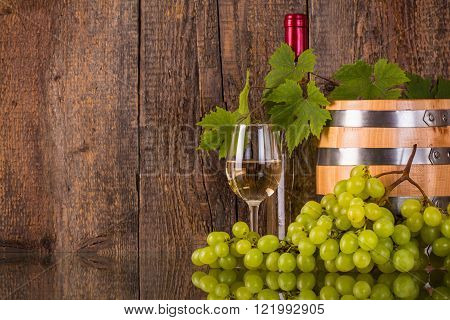 Glass of wine with a barrel white bottle hidden by grapeleaves and dark wooden background