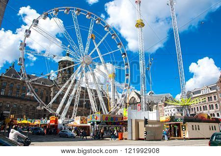 AMSTERDAM-APRIL 30: Dam Square with big wheel and Royal Palace on the background on April 30 2015 in Amsterdam Netherlands.