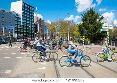 AMSTERDAM-APRIL 30: Undefined people cycle on Amsterdam street on April 302015 the Netherlands. There are more bicycles then people in Amsterdam.