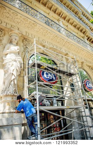MARSEILLE FRANCE - JUL 18 2014: People on scaffolding repairing the Hotel du louvre building and cleaning restoring the ancient statues on the front of the building