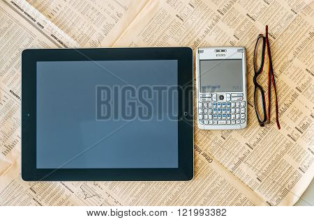 LONDON UNITED KINGDOM - MARCH 20 2014: Modern iPad Tablet computer and old QWERTY smartphone above the Financial Times magazine with worldwide stock exchange quotations and prices - next to modern vision eye wear glasses