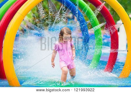 Happy little toddler girl running through a fountain having fun with water splashes in a swimming pool enjoying day trip to an aqua amusement park during summer family vacation
