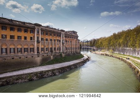 Green water of river Tiber surrounding the Island with historical buildings. Trees alley on the right riverbank. Cloudy blue sky.