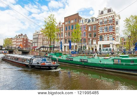 Amsterdam-April 30: Boat trip through Amsterdam canals with houseboats along the canal, people enjoy sightseeing on April 30,2015, Netherlands.