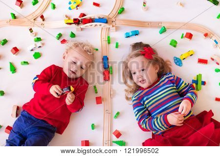 Children playing with wooden train. Toy railroad. Toddler kid and baby play with blocks trains and cars. Educational toys for preschool and kindergarten child. View from above kids on the floor.