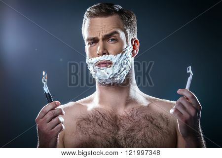 Studio portrait of handsome young man. Man with naked torso and shaving foam on face looking at camera and choosing between two razors