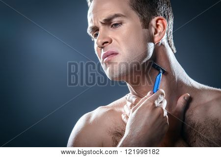 Studio portrait of handsome young man. Man with naked torso having skin irritation while using disposable razor