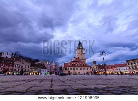 Brasov Romania - February 23: The Council Square on February 23 2016 in Brasov Romania. Panoramic view with famous buildings beautiful sky in wintertime and few blurred tourists.