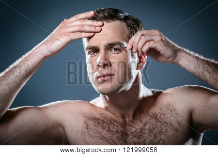 Studio portrait of handsome young man. Clean shaven man with naked torso looking at camera and tweezing eyebrows