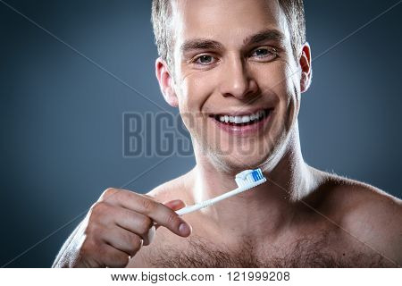 Studio portrait of handsome young man. Clean shaven man with naked torso looking at camera, smiling and holding toothbrush