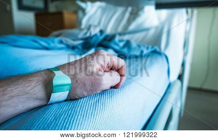 Detail Of A Man's Arm On A Hospital Bed With Wrist Tag