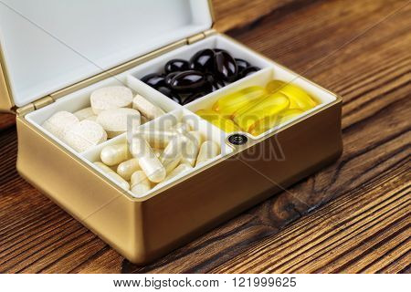Mixed natural food supplement pills in container omega 3 vitamin c carotene capsules on wooden background selective focus