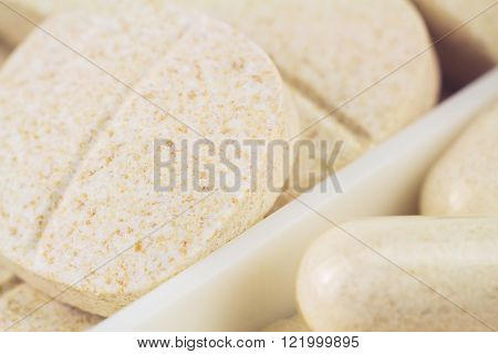 Mixed natural food supplement pills vitamin c glucosamine capsules macro image selective focus