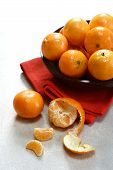 stock photo of satsuma  - a bowlful of satsuma oranges arranged on red folded placemat - JPG