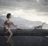 Junge Frau und Katze auf einem Baumstamm