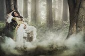 Fine art photo of a gorgeous lady in a mysterious foggy forest