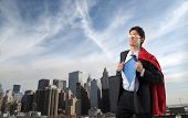Businessman disguised in superman with cityscape on the background