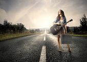 Woman holding a guitar standing on a countryside road