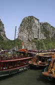 Limestone outcrops in Ha Long Bay and tourist boats poster