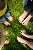 Healthy feet series: feet of men and women of different ages standing in a circle in the grass with