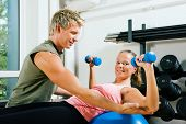 stock photo of personal trainer  - Woman lifting dumbbells on a fitness ball in a gym assisted by her personal trainer - JPG
