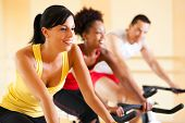 stock photo of exercise bike  - three people in the gym exercising on cycles - JPG