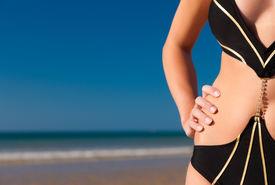 image of monokini  - Attractive Woman in monokini standing in the sun on beach - JPG