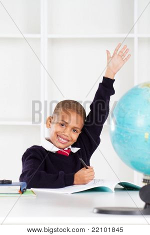 first grade student raising his hands in classroom