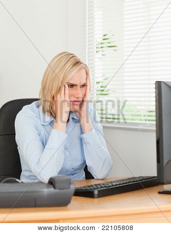 Frustrated working woman looking at a screen in an office