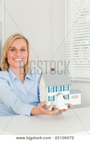 Smiling businesswoman showing model house looking into the camera in her office